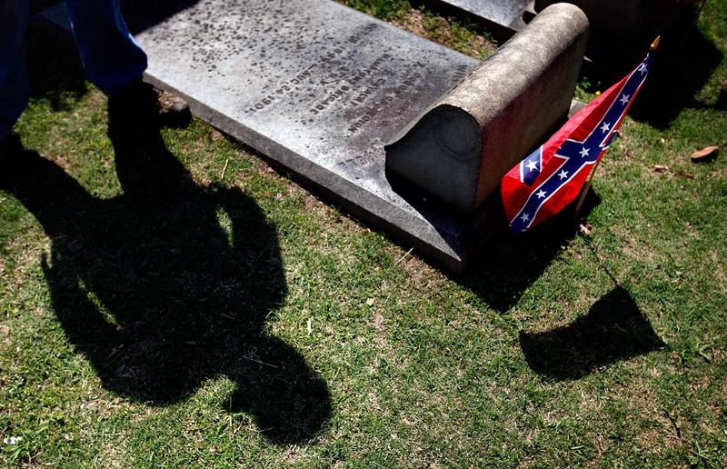A Confederate flag is planted next to the grave of Confederate soldier William Philip Mitchell as a cemetery worker pauses while walking through Oakland cemetery April 22, 2013, in Atlanta. Georgia observes Confederate Memorial Day marking the anniversary
