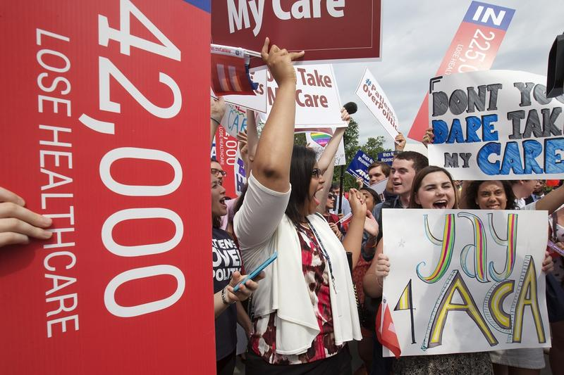 "Jessica Ellis, right, with ""yay 4 ACA"" sign, and other supporters of the Affordable Care Act, react with cheers as the opinion for health care is reported outside of the Supreme Court in Washington,Thursday June 25, 2015. The Supreme Court on Thursday uph"