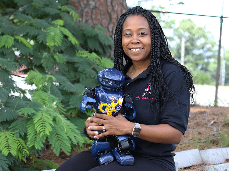 GA Tech engineering professor Ayanna Howard holds her pint-sized robot ''Yellow Jacket,'' which took her five to six years to develop.