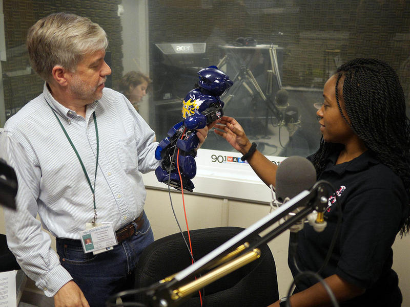 GA Tech engineering professor Ayanna Howard shows WABE's Denis O'Hayer how her robot ''Yellow Jacket'' works.