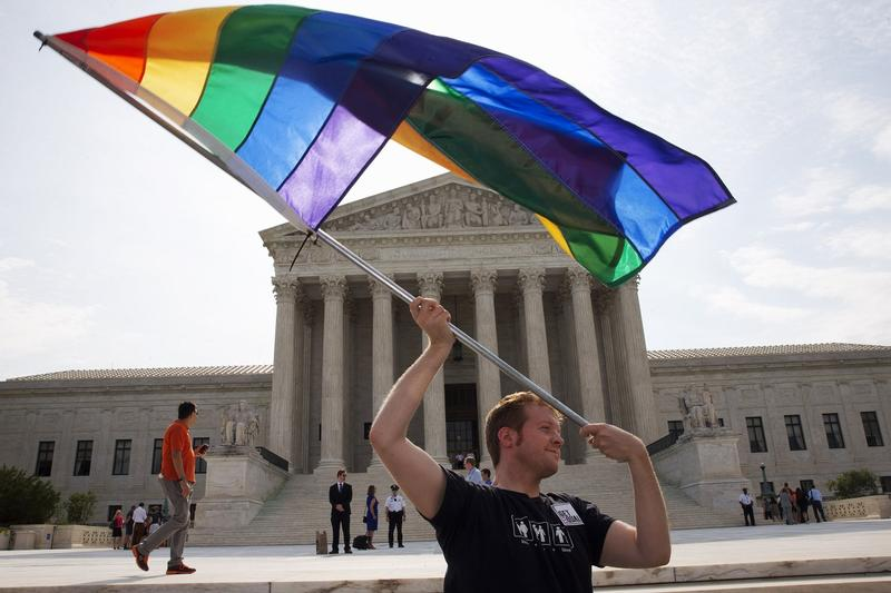 John Becker, 30, of Silver Spring, Md., waves a rainbow flag in support of gay marriage outside of the Supreme Court in Washington, Thursday June 25, 2015. The same-sex marriage ruling is among the remaining to be released before the term ends at the end