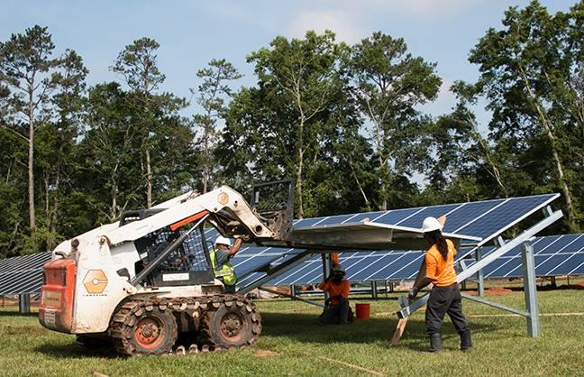 A small loader moves and lifts solar panels in Walton County.