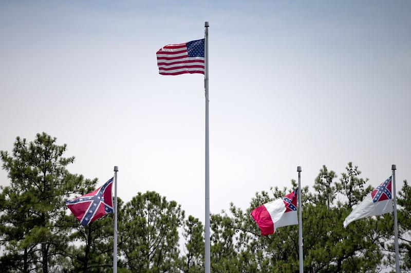 A Confederate flag, at left, flies at the base of Stone Mountain next to variations of itself and an American flag Tuesday, June 30, 2015, in Stone Mountain, Ga. At Georgia's iconic Stone Mountain, where the Confederacy is enshrined in a giant bas-relief