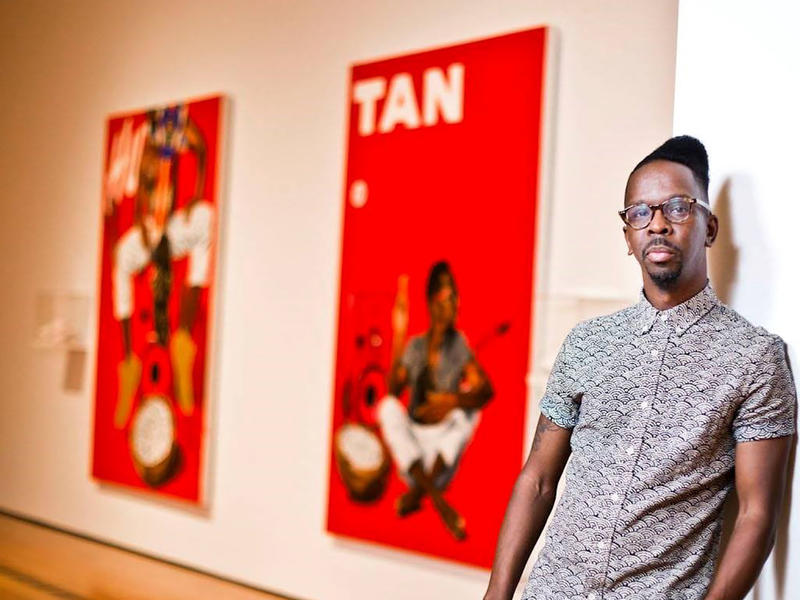 Artist, Fahamu Pecou, currently a Ph.D. student in Emory University's Institute of Liberal Arts (ILA), stands in front of his artwork at the High Museum of Art in Atlanta, Ga.