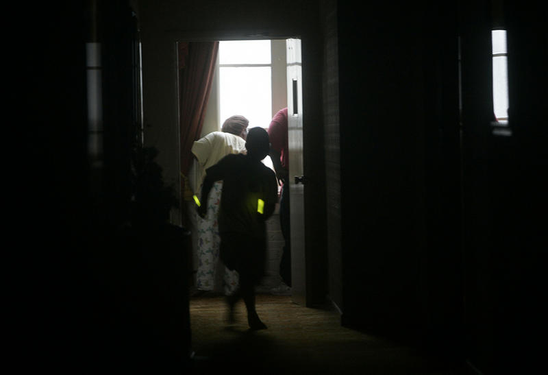 Christian Griffin, 7, uses glow sticks to negotiate through the dark halls of his hotel as he and his family monitor the progress of Hurricane Katrina as it hits New Orleans Monday morning, Aug. 29, 2005.