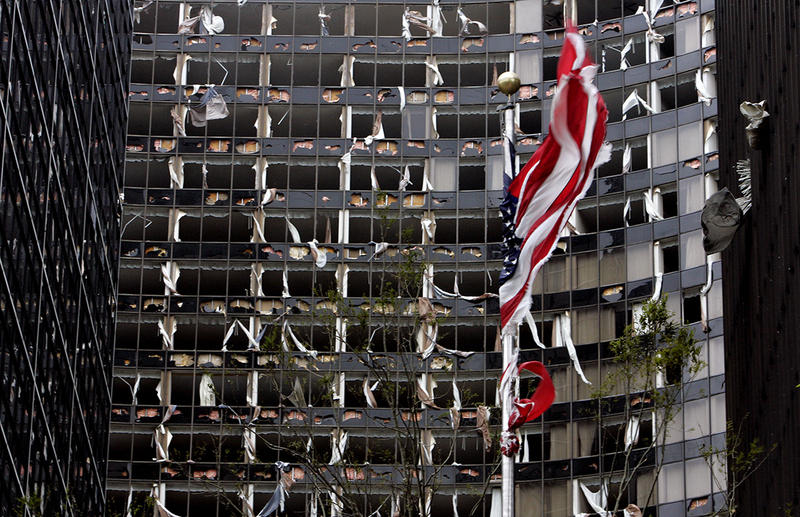 A tattered American flag flies in front of the blown out Hyatt Hotel in New Orleans after Hurricane Katrina devastated the area on Monday, Aug. 29, 2005.