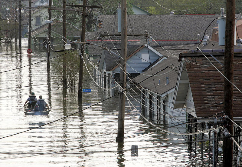 Rescue personnel search from victims as they traverse the  New Orleans 8th Ward in the flooded city of New Orleans on Tuesday, Aug. 30, 2005.
