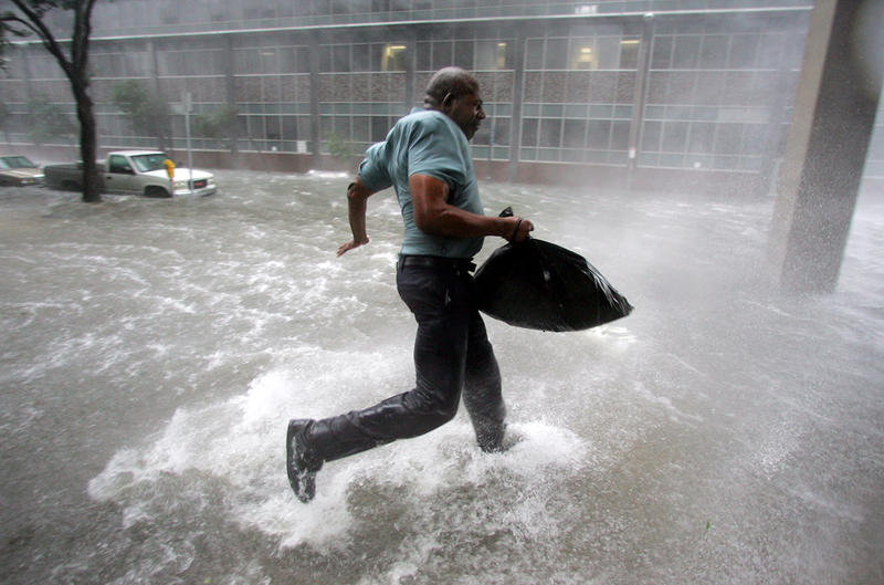 Arnold James tries to keep his feet as a strong gust nearly blows him over as he tries to make his way on foot to the Louisiana Superdome in New Orleans on Monday, Aug. 29, 2005.