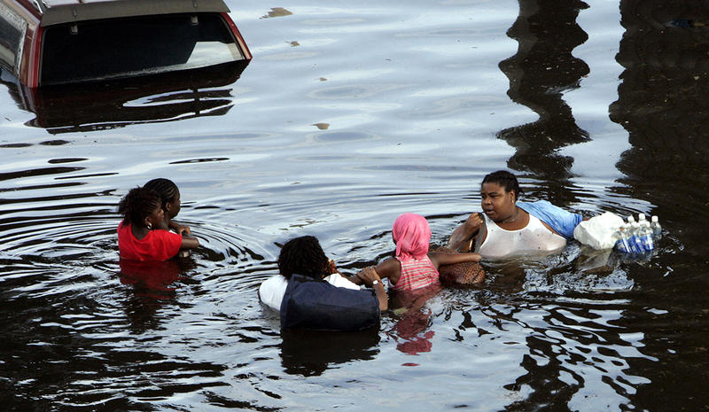 A New Orleans family tries to make their way through floodwaters in the downtown area of the Crescent City on Tuesday, Aug. 30, 2005. The water continues to rise after Hurricane Katrina pounded the area on Monday.