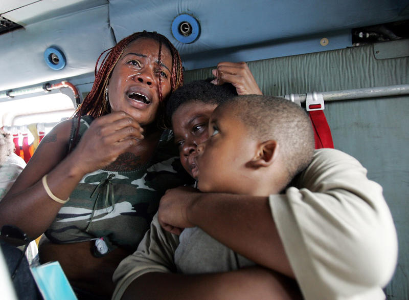 A woman cries while sitting with her two children after members of the U.S. Coast Guard transported victims of Hurricane Katrina from the Ernest N. Morial Convention Center to the airport, Saturday Sept. 3, 2005 in New Orleans, La.