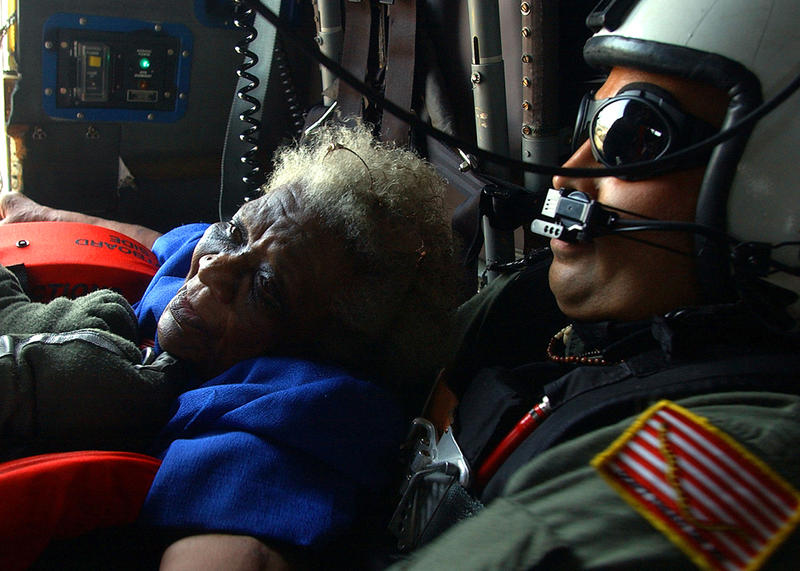 U.S. Navy search and rescue swimmer Aviation Warfare Systems Operator 1st Class Scott Chun comforts a victim of Hurricane Katrina pulled from a rooftop in New Orleans as they fly to safety aboard a U.S. Navy Seahawk helicopter in New Orleans on Sept. 5.