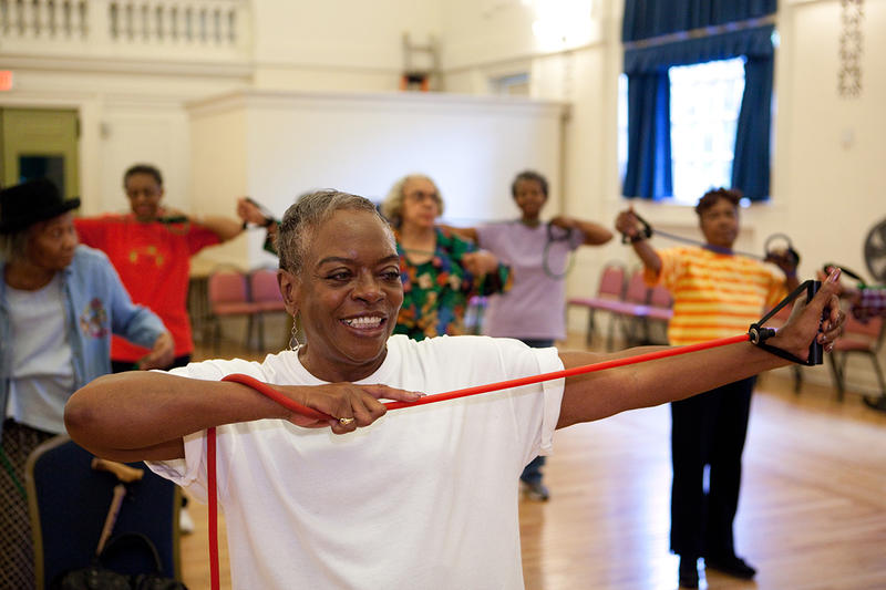 Older African-American ladies work out with strength bands.