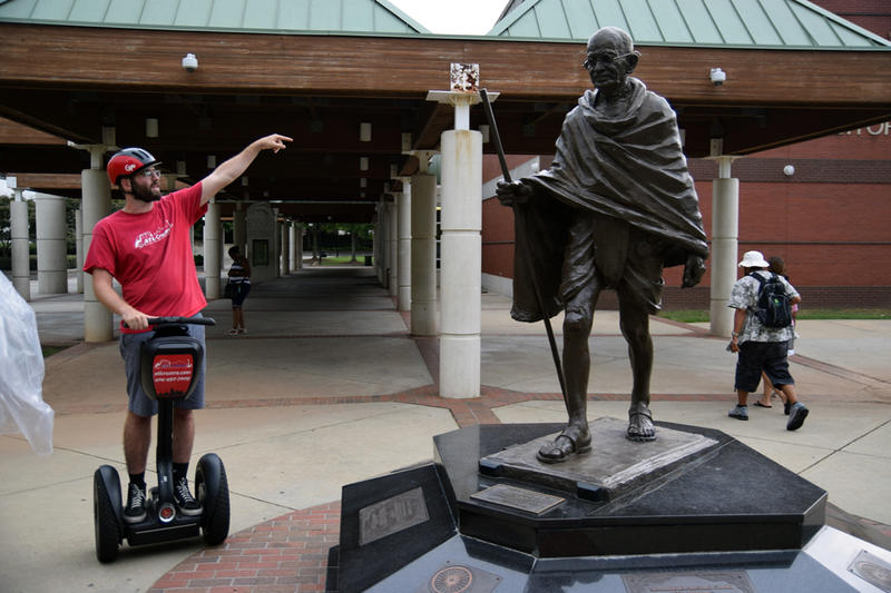 Tour guide, Andrew McClure stands on his Segway next to the Mohandas Gandhi statue at the Martin Luther King Jr. National Historic site in Atlanta.