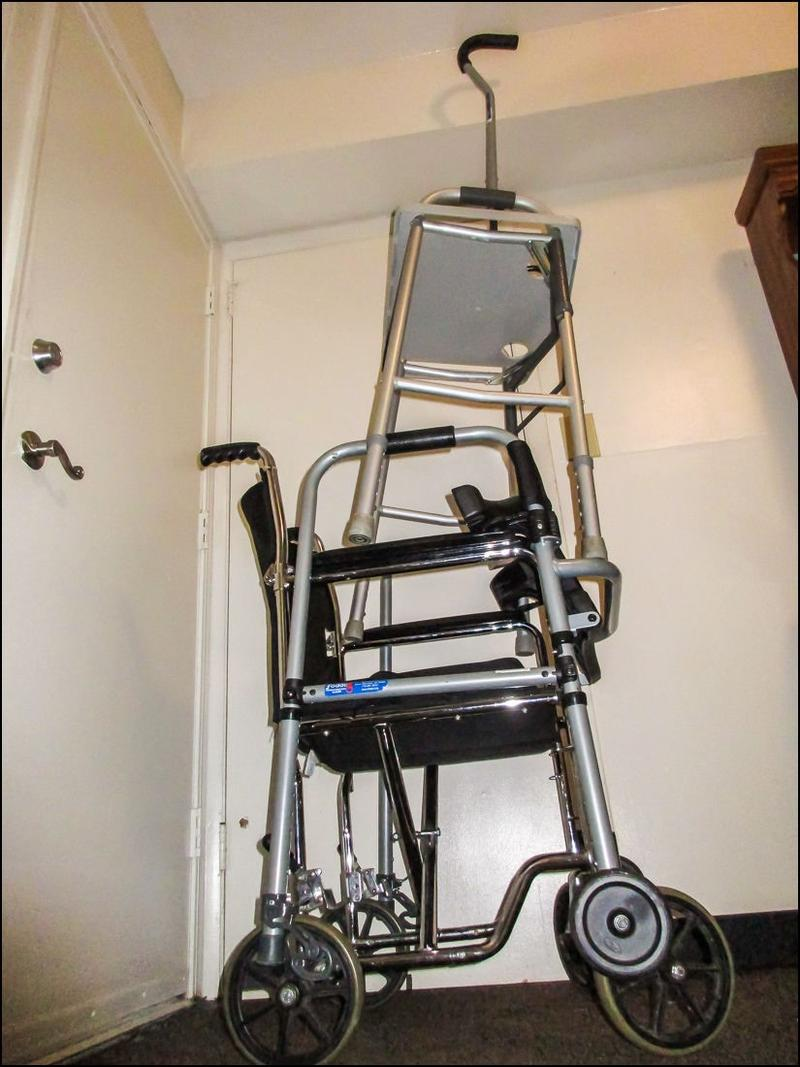 A cane, a walker, and a wheelchair are lined up against a wall at Dana Hawkins's mother's apartment. Her mother has Alzheimer's with Lewy Bodies, which means that she may need any combination of these on a given day.