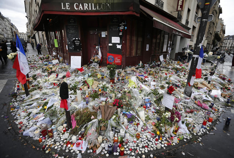Flowers and candle tributes are placed at the Restaurant Le Carillon in Paris, Thursday, Nov. 19, 2015, after last Friday's attacks.
