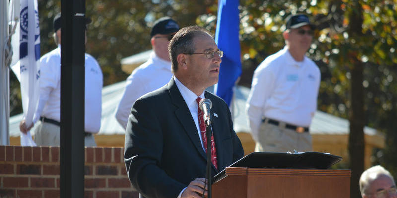 John's Creek Mayor Mike Bodker speaks at Veterans' Memorial dedication in 2014. Bodker said traffic near Johns Creek is unbearable because funding goes to MARTA and road projects get neglected. Johns Creek City Council said it opposes taxes for MARTA.