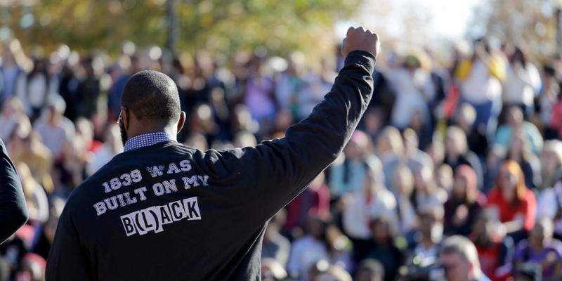 A member of the black student protest group Concerned Student 1950 gestures while addressing a crowd following the announcement that University of Missouri System President Tim Wolfe would resign Monday, Nov. 9, 2015, at the university in Columbia, Mo. Wo
