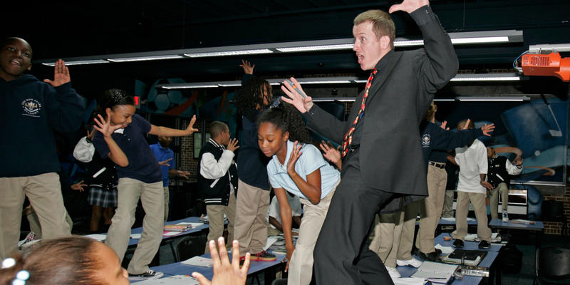 """Ron Clark dances on a desk to make a point during a seventh grade math class at the Ron Clark Academy in Atlanta on Tuesday, Dec 9, 2008. The students at the small private school scored millions of hits on YouTube last fall with a rap called """"Vote However"""