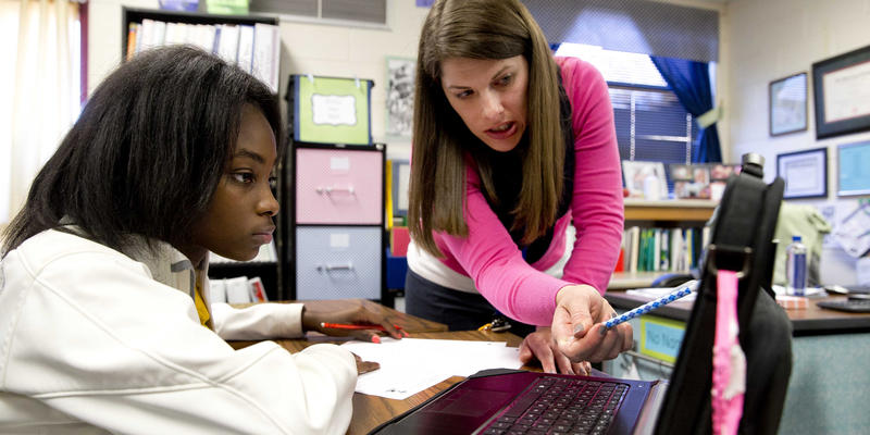 In this Nov. 20, 2014 photo, eight grader Aklya Thomas and teacher Faren Fransworth use a digital textbook to during a math class at Burney Harris Lyons Middle School in Athens, Ga.