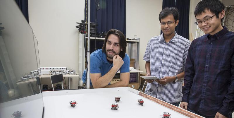 Graduate students Matt Hale, Siddharth Mayya and Li Wang used the mini-version of the Robotarium in a test session in the fall of 2015.