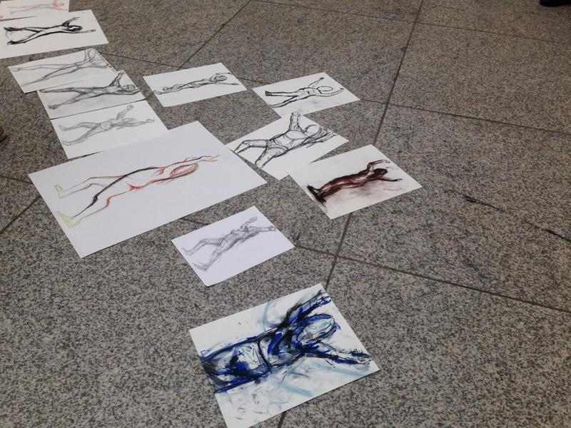 Students put the results of the five minute figure drawing challenge on the floor to be judged.