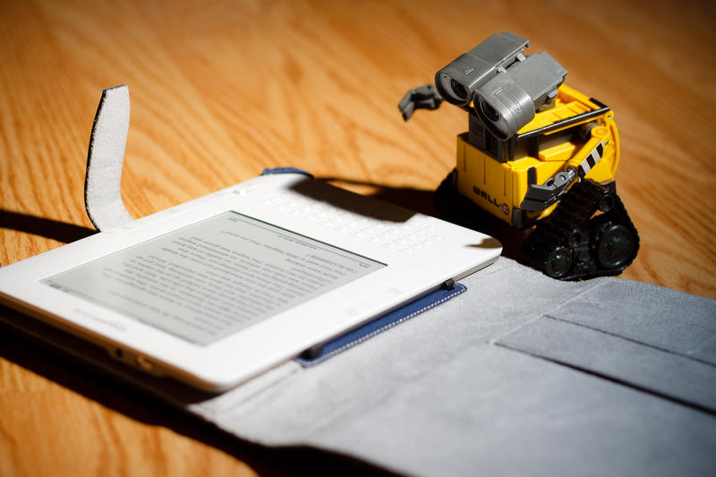 A Wall-E toy reading an e-book