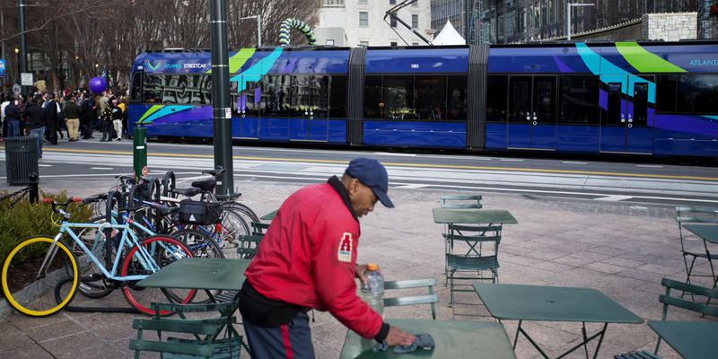 An Atlanta Streetcar sits in the background on its inaugural trip through downtown as a worker wipes tables at a park Dec. 30, 2014, in Atlanta.