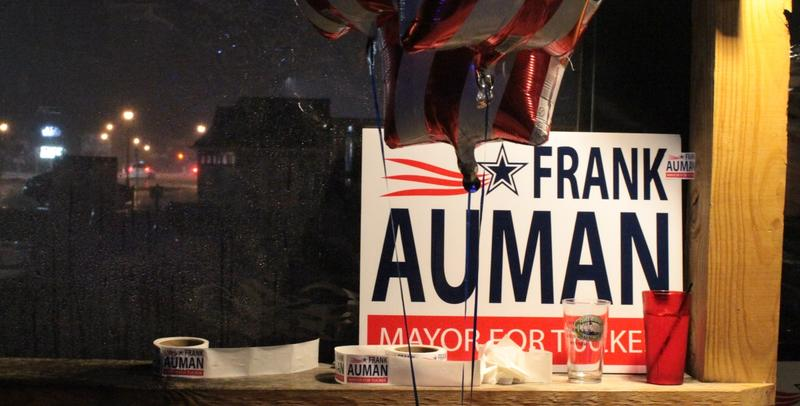 A sign for Frank Auman, leading candidate for Tucker's mayoral election, leans against a window at the Local No. 7 bar.