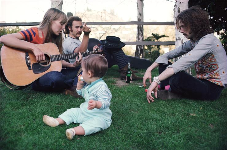 Joni Mitchell, David Crosby and Eric Clapton commune at Cass Elliott's house. Elliott's baby is in the foreground.