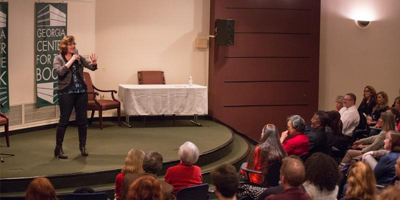 Novelist Joshilyn Jackson, shown speaking to a crowd, took some time to retreat alone.