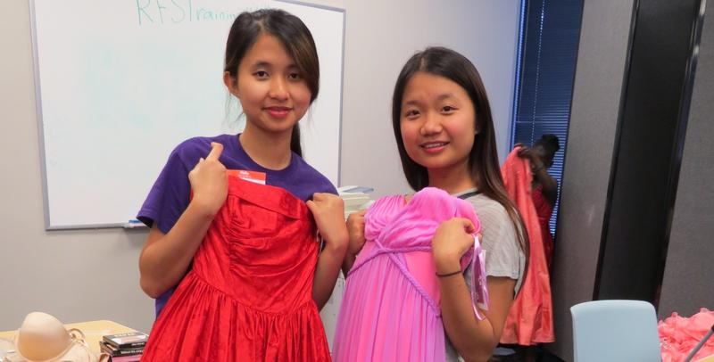 Senior Mu Ni (left) and sophomore Mary Par (right) check out the dresses donated to the New American Pathways' prom dress drive.