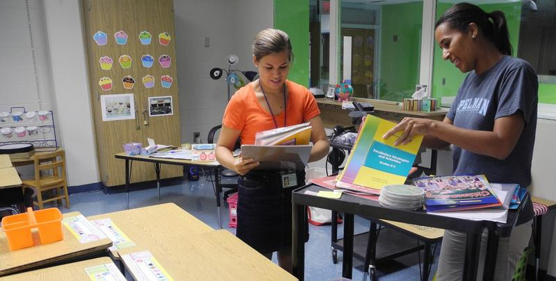 In this Thursday, Aug. 4, 2011 photo, new teacher Sarah Welch, left, receives classroom materials from veteran teacher Michele Alford at Toomer Elementary School in Atlanta.