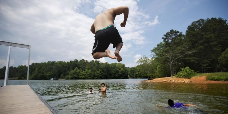 Cristian Chavez jumps into Lake Lanier while swimming with friends off Longwood Park, Monday, June 8, 2015, in Gainesville, Ga.