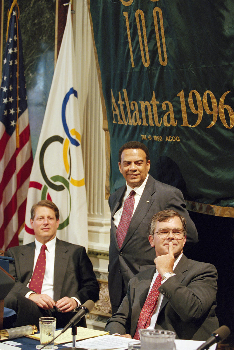 Vice President Al Gore, left, along with Billy Payne, right, CEO of the Atlanta Committee for the Olympic Games (ACOG), and co-chair of the ACOG Andrew Young, standing at center, watch a video at the White House, Aug. 2, 1995, during a meeting.