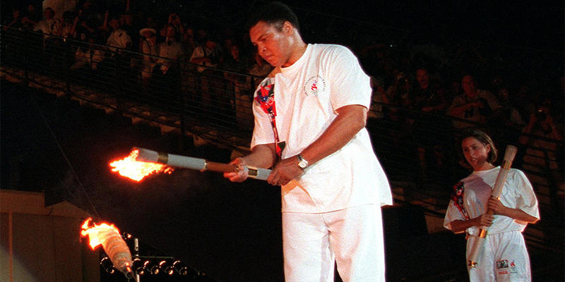 American swimmer Janet Evans looks on as Muhammad Ali lights the Olympic flame during the 1996 Summer Olympic Games opening ceremony in Atlanta July 19, 1996.