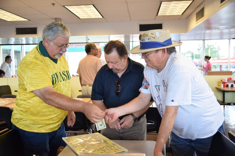 Jim Prinsen, right, wheels and deals with fellow traders over Atlanta Olympics and other Olympic pins at the Varsity in Atlanta.