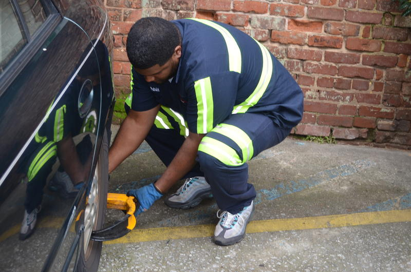 ''Booter'' Patrick Smith applies a wheel lock, nicknamed a ''boot,'' to immobilize a vehicle.