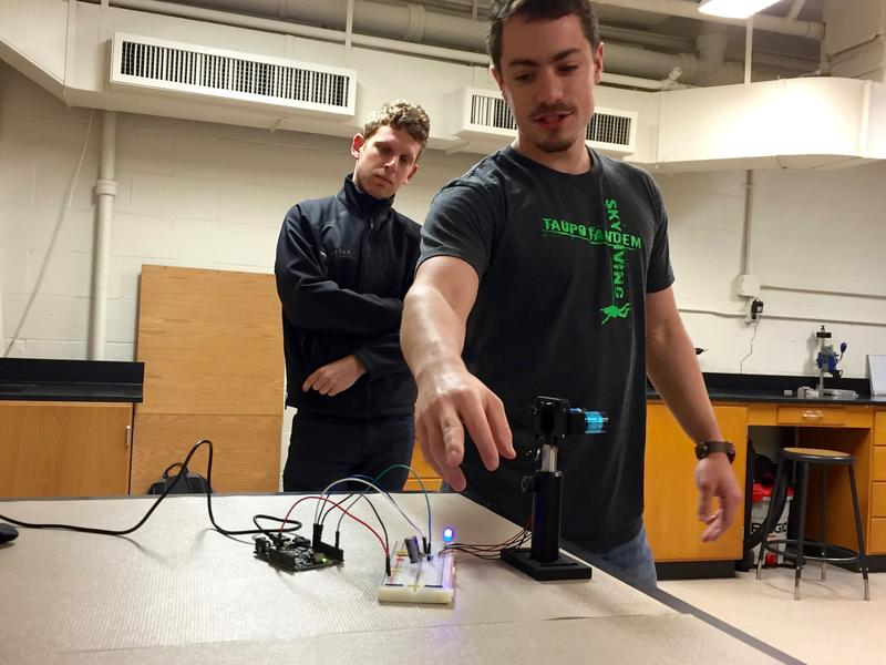 Georgia Tech computer engineering student Roy Blatt (foreground) and graduate student Zach Levine show off how optical lasers on Georgia Tech's RANGE mission satellite could be used to send messages to a second satellite using binary code.