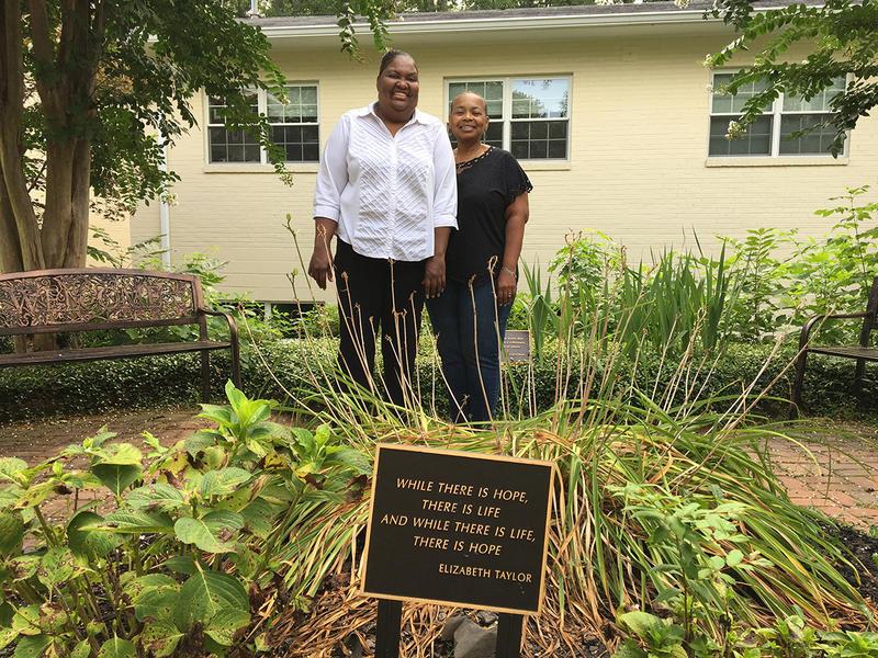 Shandora Lane and Janice Harris-Corey pose in the garden of Jerusalem House.