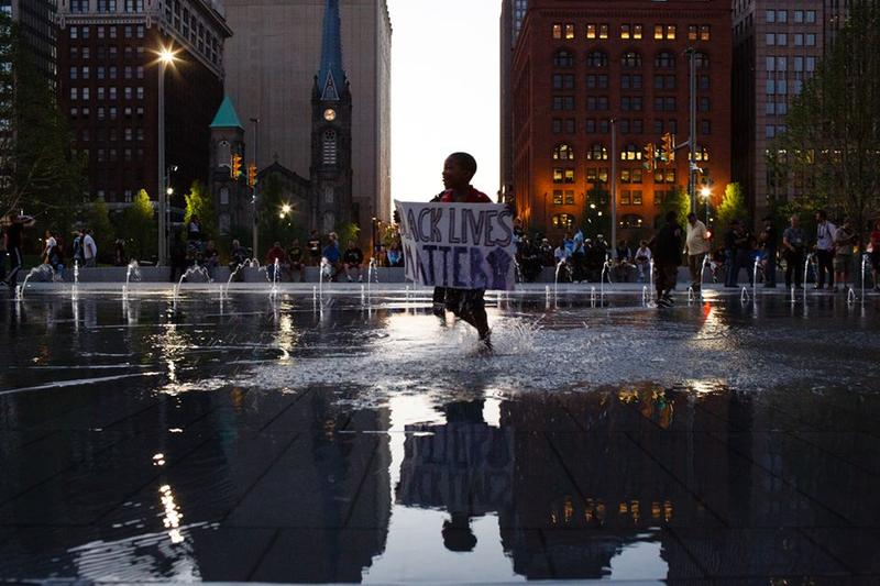 A boy carried a Black Lives Matter poster while playing in the fountain outside the Republican National Convention.