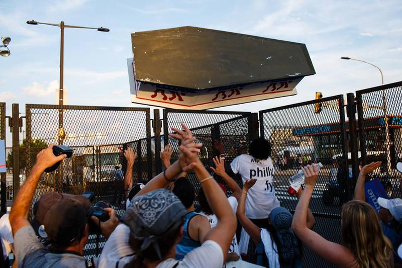 """Outside the DNC, protesters attempt to hurtle """"democracy's coffin"""" across the barrier."""