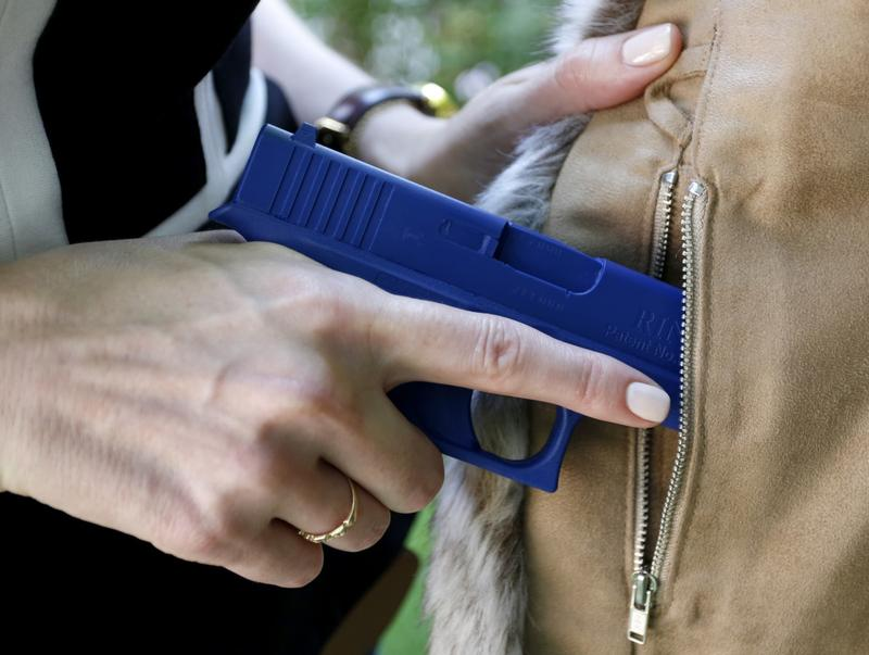 In this Aug. 29, 2016 photo, Marilyn Smolenski uses a mock gun to demonstrate how to pull a handgun out of the concealed carry clothing she designs at her home in Park Ridge, Ill.