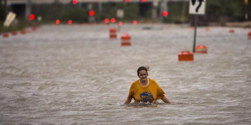 A woman who identified herself as Valerie walks along flooded President Street after leaving her homeless camp after Hurricane Matthew caused flooding, Saturday, Oct. 8, 2016, in Savannah, Ga.