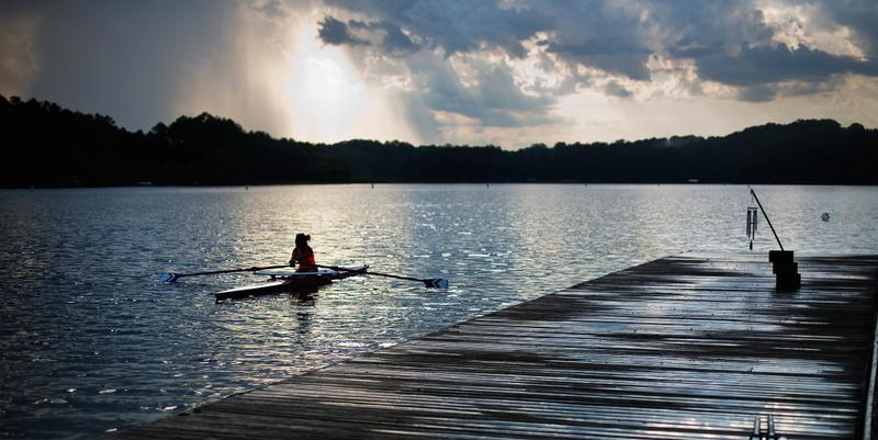 In this Tuesday, July 19, 2016 photo, a rower moves past the launching docks at Lake Lanier Olympic Park, home of the 1996 Summer Olympic Games rowing events, in Gainesville, Ga.