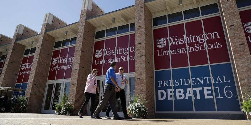 People walk by the debate site ahead of the second presidential debate at Washington University, Saturday, Oct. 8, 2016, in St. Louis. The town hall debate between Republican presidential nominee Donald Trump and Democratic presidential nominee Hillary Cl