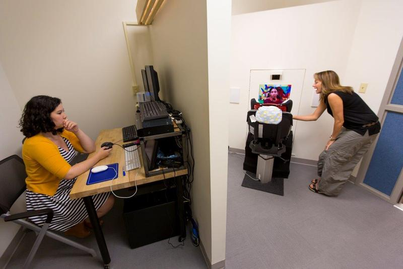 Dr. Celine Saulnier, (R), sets up a child in the toddler eye-tracking research equipment as a fellow prepares to monitor her eye movements.