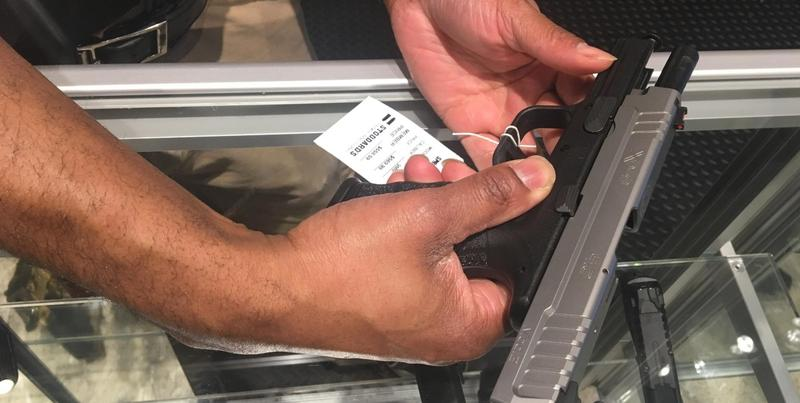 A salesman at Stoddard's Range and Guns shows off a pistol's safety features.