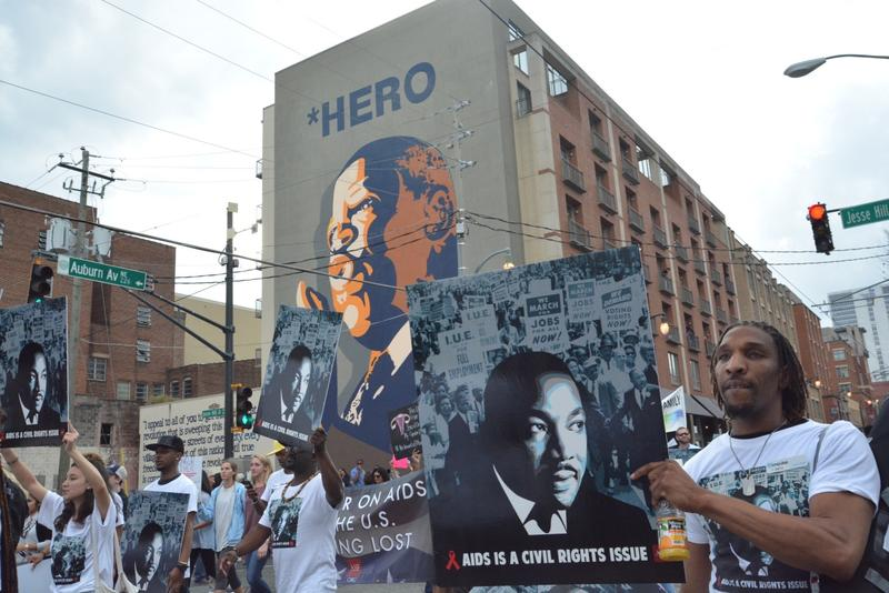 The march passes a mural depicting Rep. John Lewis above the word ''HERO.''