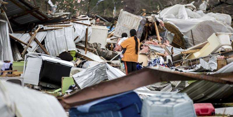 A woman holds a child while walking through a farm that was damaged by a tornado, Sunday, Jan. 22, 2017, in Adel, Ga.