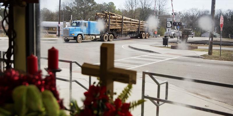 A logging truck passes through the Main Street business district as a cross stands in a flower shop window in Lula, Ga., in Hall County, Tuesday, Jan. 10, 2017.